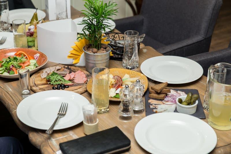 Jantar amigável grupo de pessoas que tem o jantar junto ao sentar-se na tabela de madeira imagens de stock