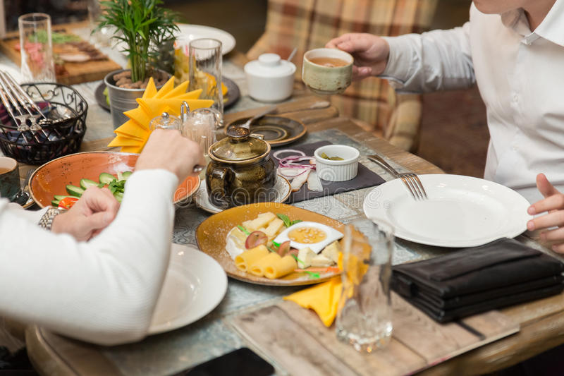 Jantar amigável grupo de pessoas que tem o jantar junto ao sentar-se na tabela de madeira fotos de stock royalty free