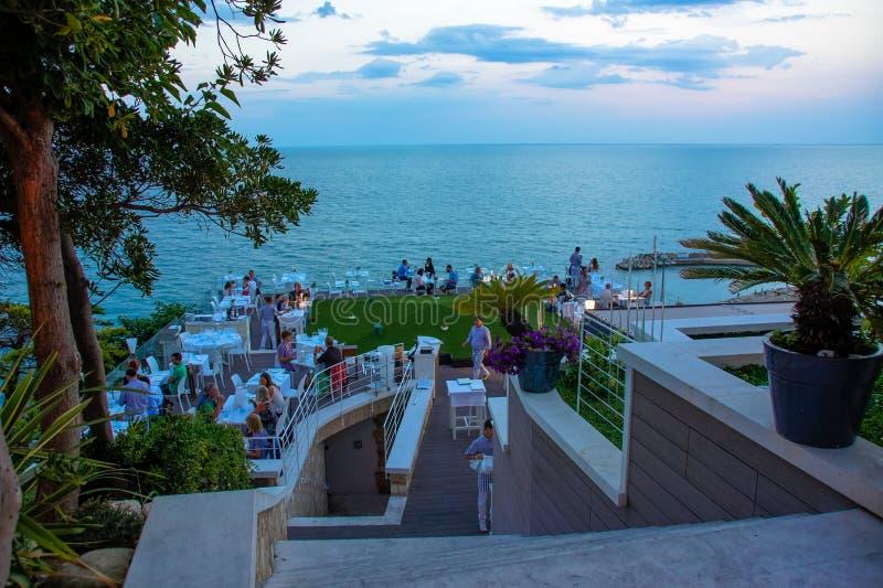 Jantar da noite em um restaurante que negligencia o mar Vista na costa adriático em Numany, Itália fotografia de stock royalty free