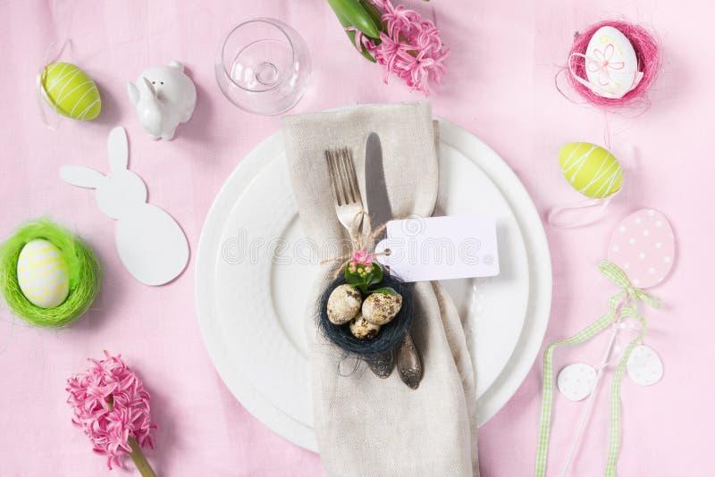 Jantar da Páscoa Ajuste elegante da tabela com as flores da mola na toalha de mesa cor-de-rosa Vista superior foto de stock royalty free