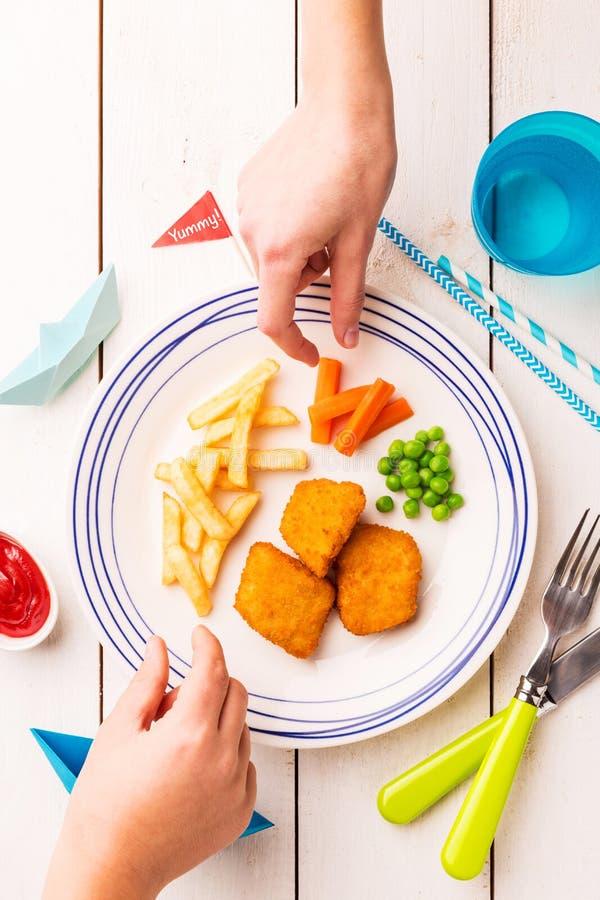 Jantar da refei??o da crian?a - peixe, microplaquetas, cenoura e ervilhas verdes fotografia de stock
