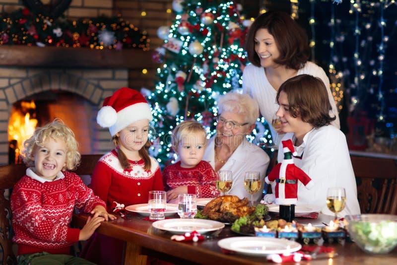 Jantar do Natal Família com as crianças na árvore do Xmas fotos de stock