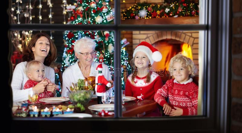 Jantar do Natal Família com as crianças na árvore do Xmas imagem de stock