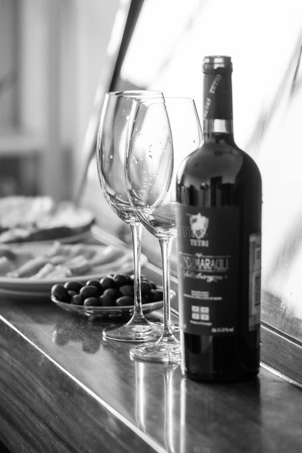 Jantar e vinho tinto românticos os pratos estão no piano: peixes, azeitonas, vidros bw, vertical foto de stock royalty free