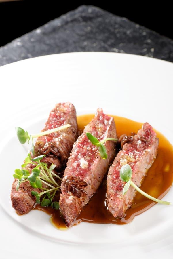 Jantar fino, faixas de Angus Beef Steak com tomate Roasted fotografia de stock royalty free