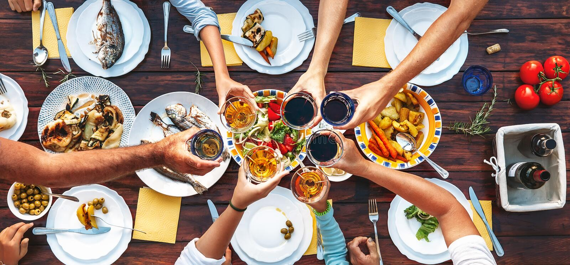 Jantar grande da família Vista superior vertical na tabela e nas mãos servidas w imagem de stock