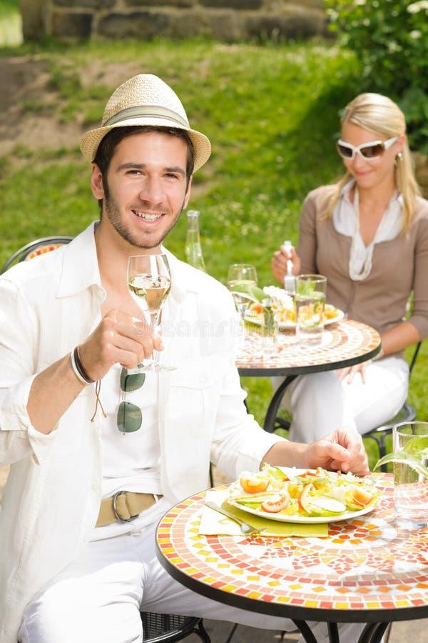 Jantar italiano do homem novo do restaurante ensolarado do terraço foto de stock