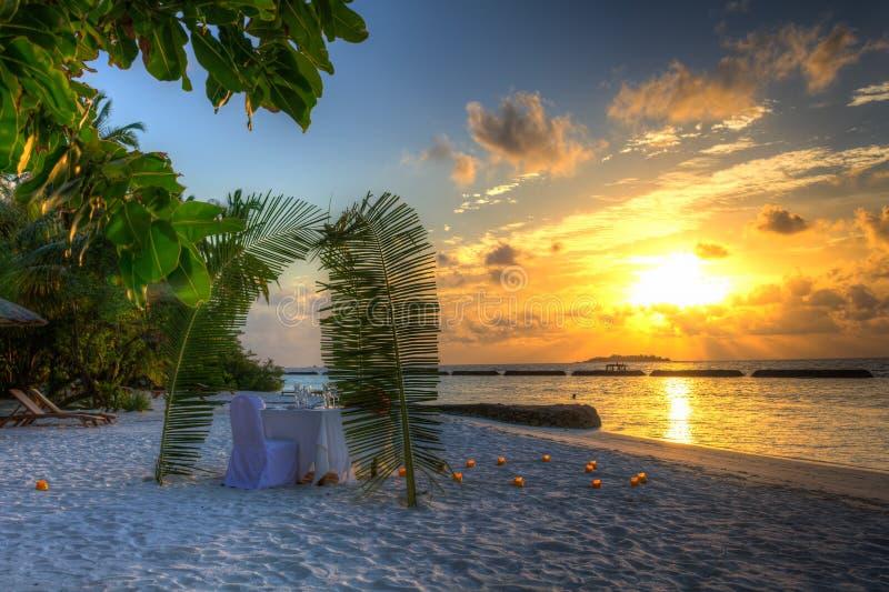 Jantar na praia pelo por do sol fotografia de stock royalty free