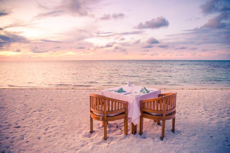 Jantar romântico da praia Tabela para dois por do sol idílico, recurso tropical ou hotel, praia do por do sol imagem de stock