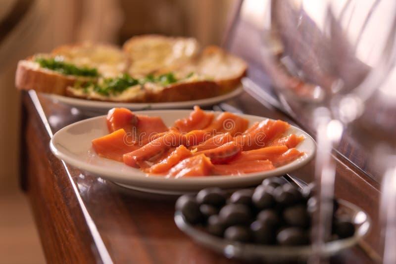 Jantar rom?ntico os pratos estão no piano: peixes, azeitonas, vidros fotos de stock royalty free