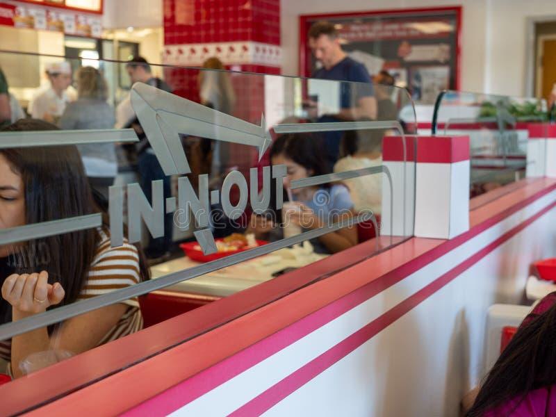 Jantares que comem -n-para fora no lugar do hamburguer atrás do logotipo no divisor de vidro foto de stock royalty free