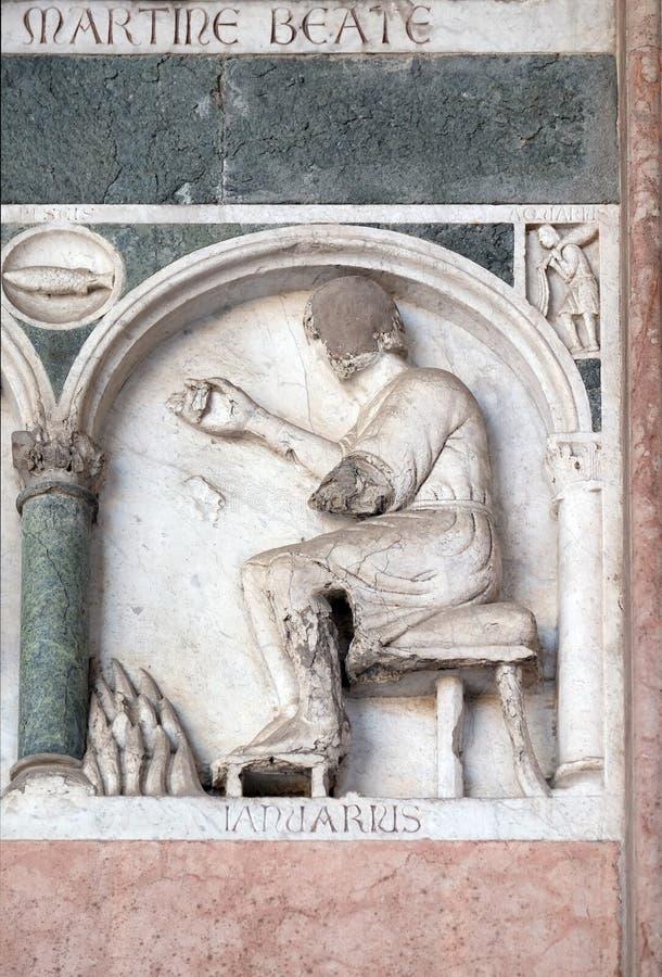 Januari, detail van de bas-hulp die de Arbeid van de maanden van het jaar, Kathedraal in Luca, Italië vertegenwoordigen royalty-vrije stock foto's