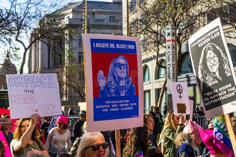 Januari 19, 2019 San Francisco/CA/USA - deltagare till kvinnornas tecknet för håll för marshändelse med olika politiska meddeland royaltyfri fotografi