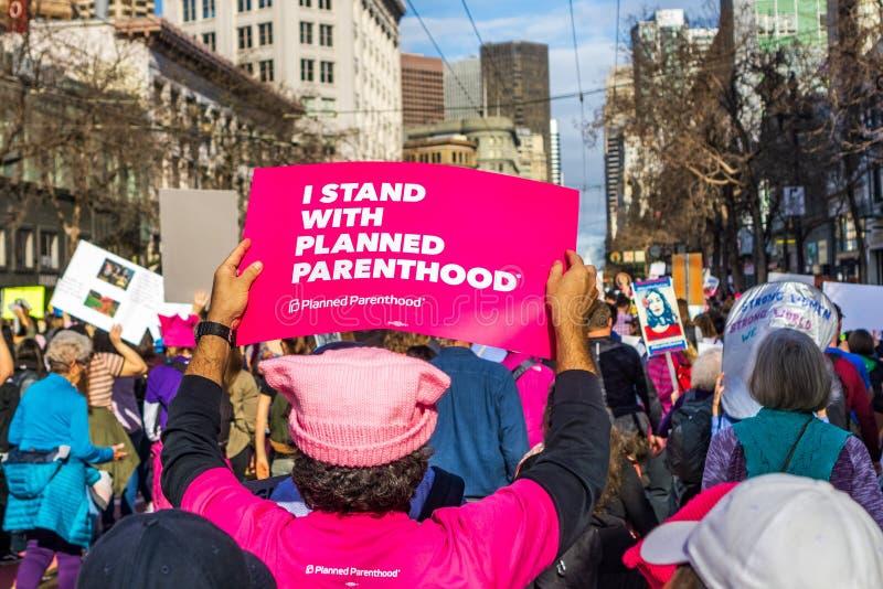 Januari 19, 2019 San Francisco/CA/USA - kvinnors marschers ställning för I med tecknet för planerat föräldraskap ' royaltyfri bild