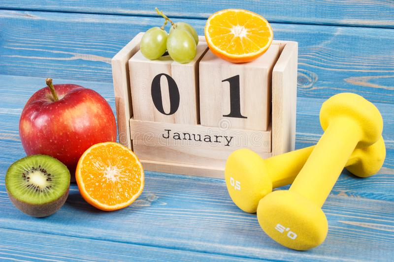 January 1 on cube calendar, fruits and dumbbells, new years resolutions concept. January 1 on cube calendar, fresh ripe fruits and dumbbells for fitness, new stock photography