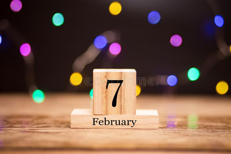 February 7th. Day 7 of february month set on wooden calendar at center of dark background with garland bokeh. Winter time. Empty space for text, mockup stock image