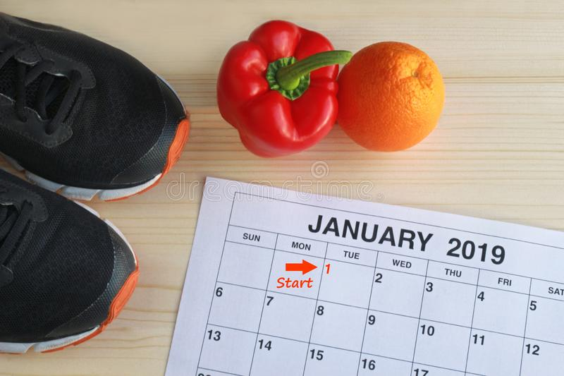 January 2019 Start in a new healthy life. January 2019 - Start in a new healthy life, calendar page of january, jogging shoes, a red pepper and an orange on a royalty free stock photos