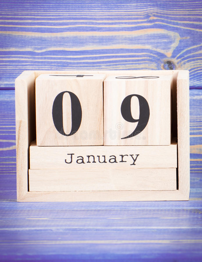 January 9th. Date of 9 January on wooden cube calendar. Purple board as background stock image