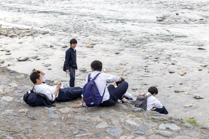 Japão, Arashiyama, 04/06/2017 Uma empresa dos estudantes japoneses que relaxam na natureza imagens de stock royalty free