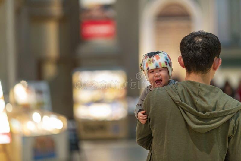 Japão, Tóquio, 04/08/2017 Uma criança asiática de grito nos braços do paizinho fotografia de stock royalty free