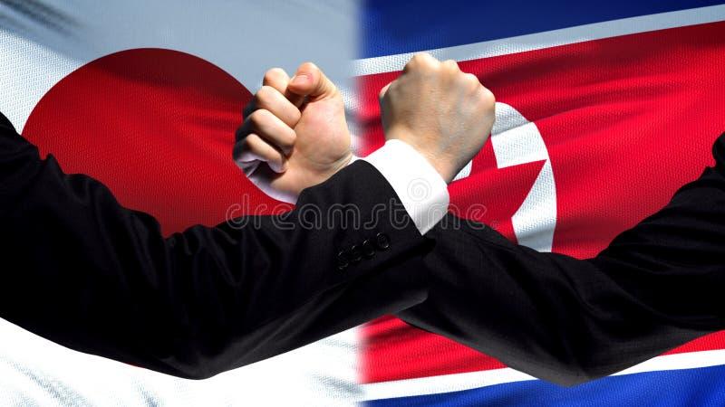 Japón contra la confrontación de Corea del Norte, intereses está en conflicto, los puños en fondo de la bandera foto de archivo