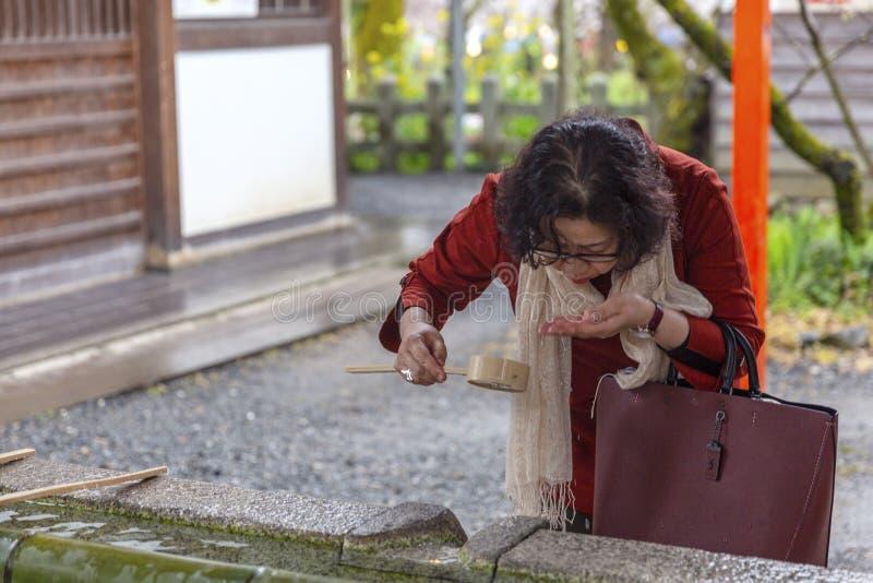 Japón, Kyoto, 04/07/2017 La mujer japonesa bebe el agua santa de un tanque tradicional en un parque fotografía de archivo
