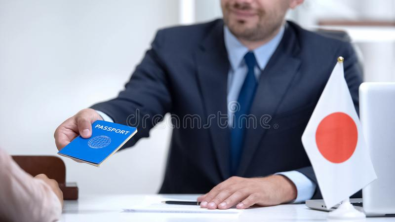 Japan consular officer giving passport to young woman, student visa approval stock photo