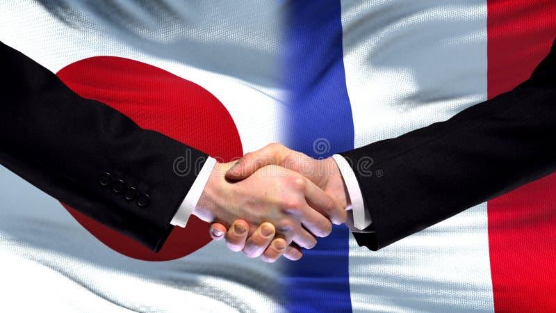 Japan och Frankrike handskakning, internationell kamratskapförbindelse, flaggabakgrund arkivfoto