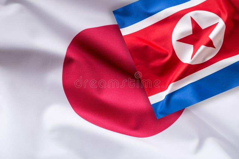 Japan och Nordkorea flagga Färgrik Japan och Nordkorea flagga royaltyfri foto