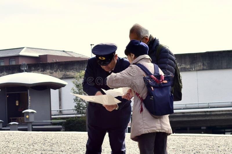 Japan-Polizist, welche alten Paaren hilft lizenzfreie stockfotografie