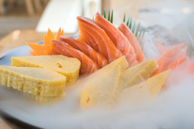Japan raw salmon sashimi, sweet egg and imitation crab stick on ice pod in Japanese food restaurant. Fresh Japanese food concept stock photography