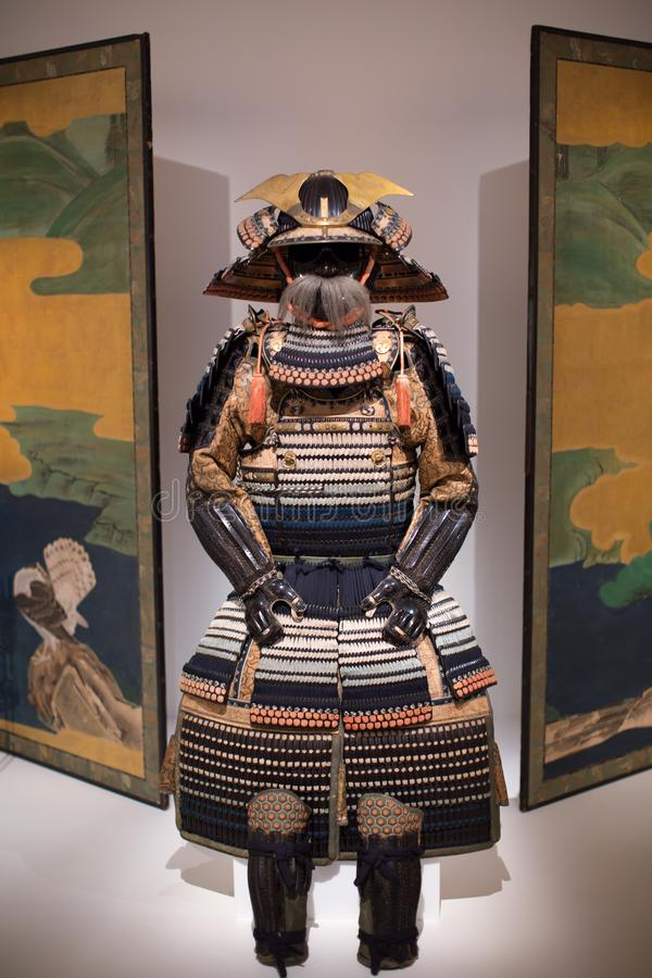 Japan Samurai Armor and Traditional Tapestry. A complete traditional samurai armor in display between two hung traditional tapestry / art piece stock images