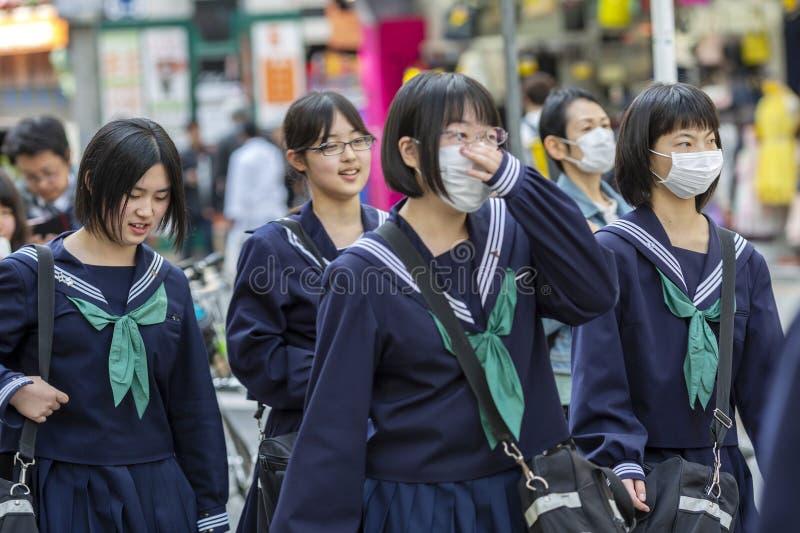 Japan Tokyo, 04/12/2017 En grupp av japanska skolflickor på en stadsgata arkivbilder