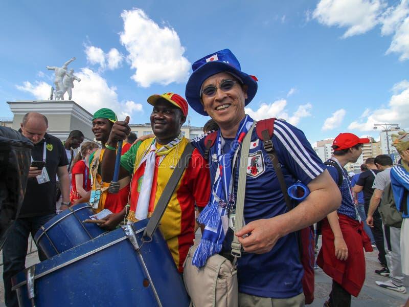 Japan- und Senegal-Fanfußball macht Fotos zusammen lizenzfreie stockfotos