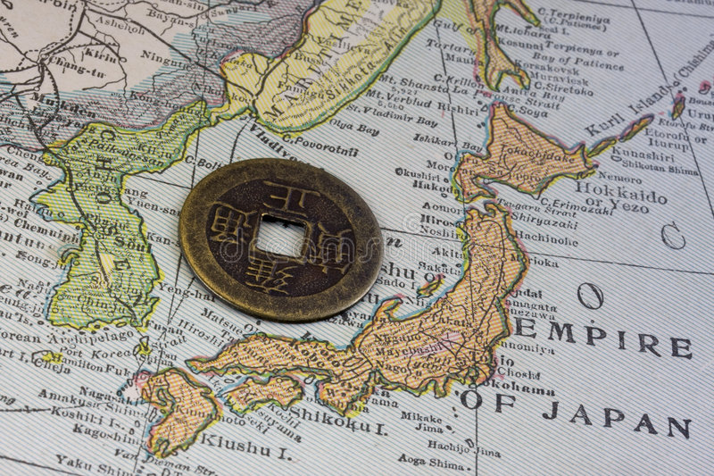 Japan on vintage map and old coin. Empire of Japan on a vintage map (1926) and old Japanese coin with square hole stock photo