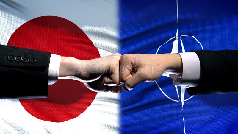 Japan vs NATO conflict, international relations crisis, fists on flag background royalty free stock photography