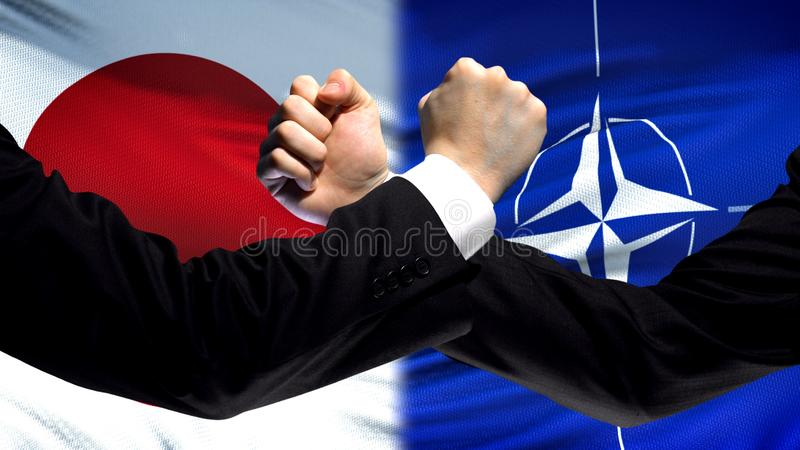 Japan vs NATO confrontation, countries disagreement, fists on flag background royalty free stock photography