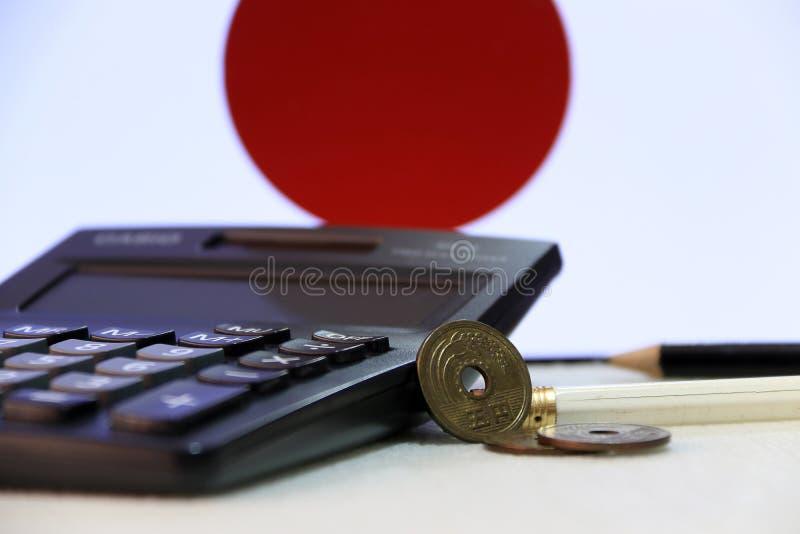 Japaner fünf Yen drei Münzen JPY auf weißem Boden mit schwarzem Taschenrechner und Bleistift auf Japan kennzeichnen Hintergrund stockfotografie
