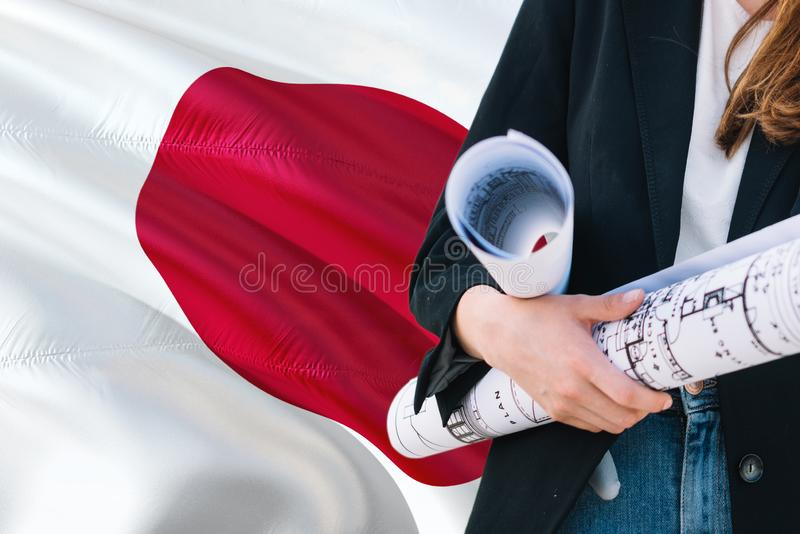 Japanese Architect woman holding blueprint against Japan waving flag background. Construction and architecture concept royalty free stock photography
