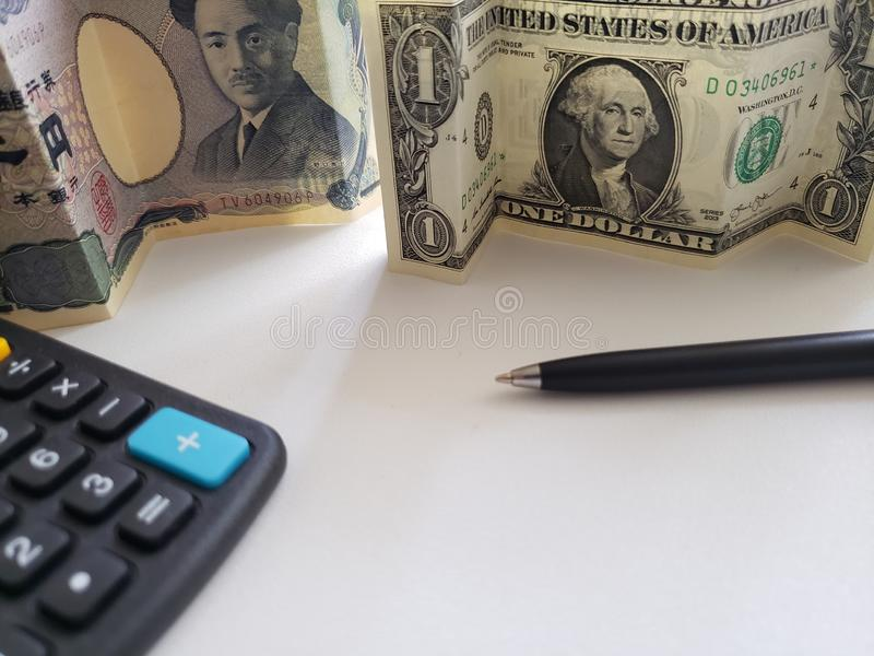 Japanese banknote of 1000 yen, American one dollar bill, black pen and calculator stock photo