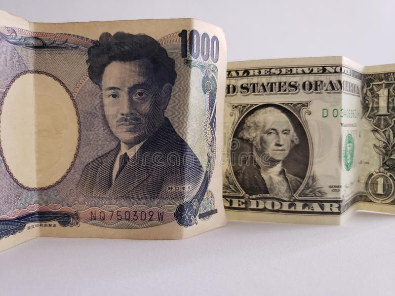 Japanese banknote of 1000 yen and American one dollar bill stock images