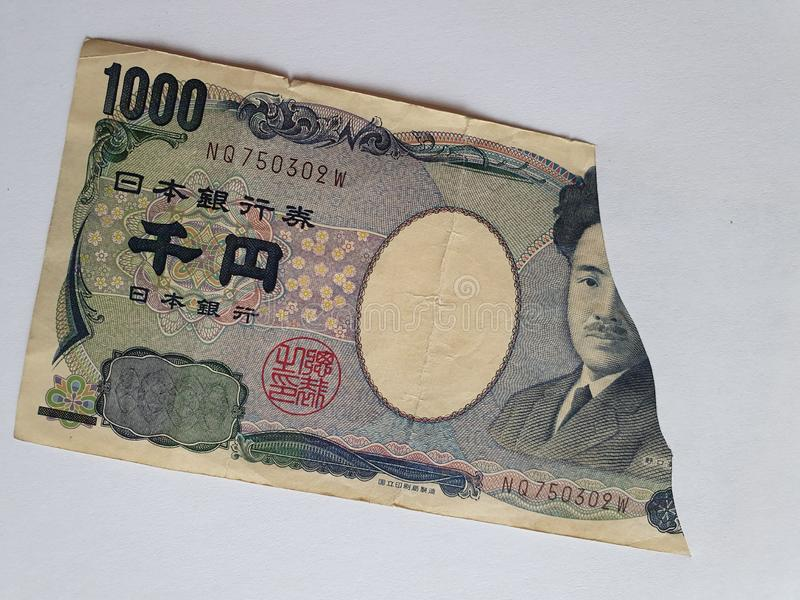 Japanese banknote of 1000 yen on the broken sheet of paper. Commerce, exchange, trade, trading, value, buy, sell, profit, price, rate, cash, currency, paper stock photos