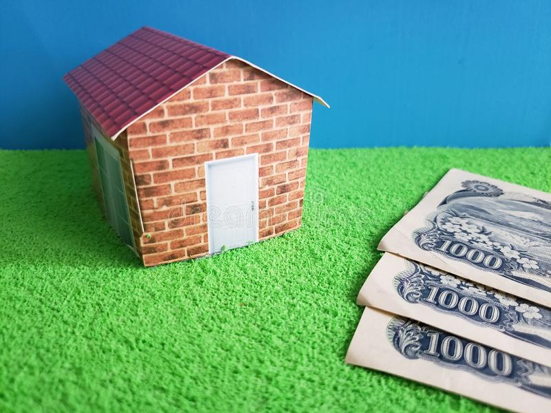 japanese banknotes and figure of a house on green surface and blue background stock image