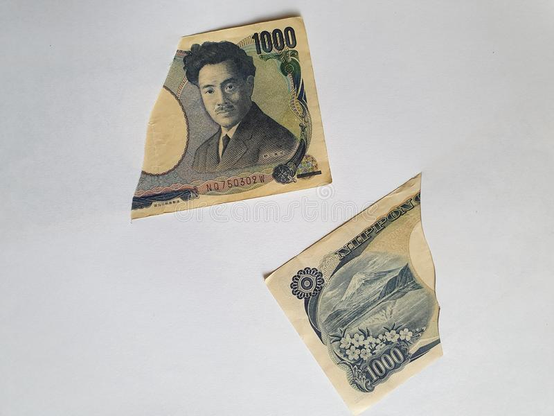 Japanese banknotes of 1000 yen on the broken sheet of paper. Commerce, exchange, trade, trading, value, buy, sell, profit, price, rate, cash, currency, paper stock image