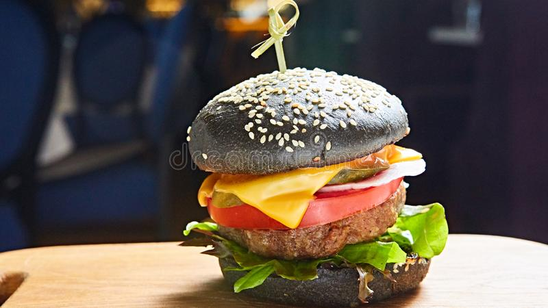Japanese Black Burger with Cheese. Cheeseburger from Japan with black bun on dark background. royalty free stock images