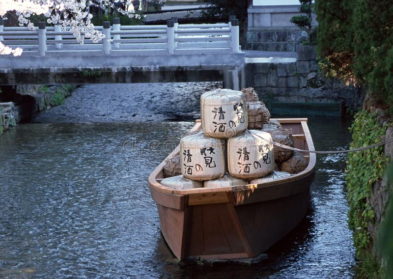 Japanese boat with goods in a river tied to the bank with a rope background royalty free stock image