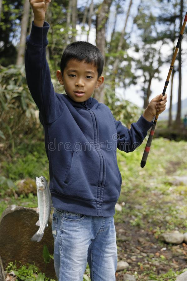 Japanese boy catching fish. Fourth grade at elementary school royalty free stock photos