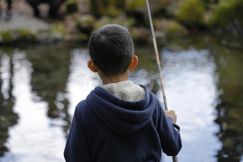 Japanese boy catching fish. Fourth grade at elementary school stock photos