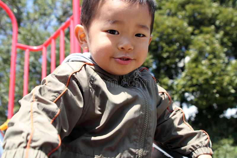 Japanese boy on the slide. (2 years old royalty free stock image