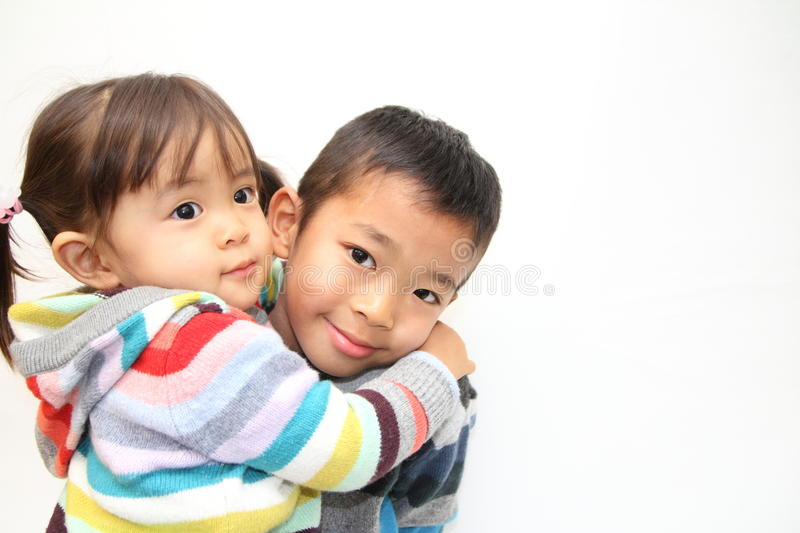 Japanese brother and sister hugging each other. 7 years old boy and 2 years old girl stock photos